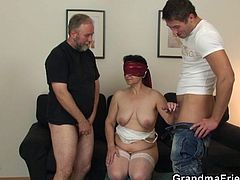Granny Tatana stays bent over, as her old guy plays with a dildo in her pussy. He slides the sex toy deep in her vagina and makes the whore, all turned on. Then he blindfolds her and prepares something very special. The guy invites a much younger dude and they both, fuck grandma's mouth. She loves it!
