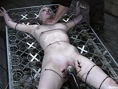 Blonde girl sits on the floor being tied up and gagged. She gets her pussy toyed. She also gets toyed on a bondage bed.