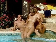 A lucky dude gets fucked by two insatiable blondes on the poolside