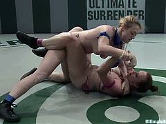 Two nasty girls in bikini fight in Ultimate Surrender video. The brunette girl gets her hair pulled and pussy toyed rough with a strap-on right in a ring.