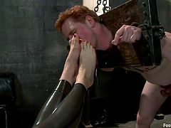Beautiful blonde milf Lorelei Lee, rubs her foot on her slaves cock, while jacking him off. She moves on to another slave, who is locked in stocks. She sticks her boots in his face and makes him suck on the long heel. She takes off her boots and the slave, must smell and lick her sweaty feet.