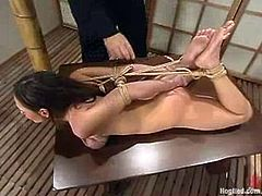 Nasty brownie lies on a table being tied up. Later on she also gets her tits twisted so that they become vinous. After that she also gets her pussy fingered by her master.