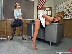 Chanta-Rose and Shannon Kelly are having BDSM fun in a classroom. The dominatrix binds the milf and spanks her ass before drilling her cunt with a strapon.