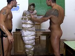 Raunchy college student is sexually exploited by two horny teachers. She sucks hard dick deepthroat while getting rammed bad in her butt hole doggy style. Perverted men also wrap her with plastic tape.