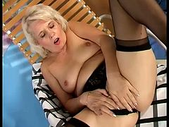 Hot mature blonde Leona wearing black stockings is having some good time indoors. She fingers her vag passionately and then rubs it with a dildo.