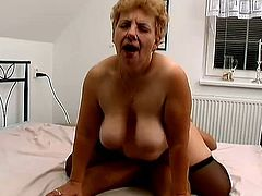 Salacious blonde granny Kat is having fun with some guy in a bedroom. She sucks and rubs the man's wang and then they have sex in the reverse cowgirl position.