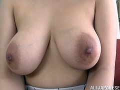Busty Japanese chick Yuna Nanjyou shows her huge natural boobs. Then she kneads and oils her jugs and takes a realistic toy in between them.