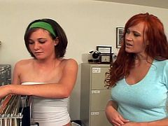 The busty redhead makes a move on the young brunette babe. She licks her shaven pussy and then they play with different toys. They use the desk as their crazy nest.