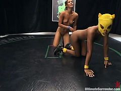 Hot Isis Love and a girl in yellow mask wrestle in a ring. Yellow Kitty gets fingered and spanked because she loses a fight. After that she also gets toyed with a strap-on.
