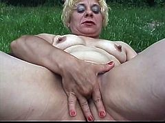 Short-haired blonde granny is playing dirty games in the garden. She lies on the grass with her legs moved wide apart and fingers her snatch before drilling it with an oversized dildo.