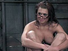 Busty brown-haired chick Eva Angelina lets some man bind her in a basement and play with her tits and pussy. The dude pulls the cutie by the nipples and then fucks her vag with a dildo.