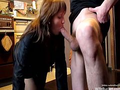 This mature babe is a real wife who blows her husband's cock in the kitchen. She kneels when she feeds on his cock and he holds her hair for a better view.