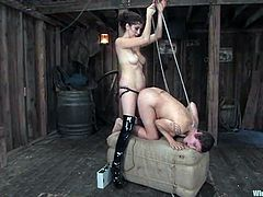 Bosomy brunette milf Saffron gets bound in a basement. Then the mistress attaches electric wires to Saffron's tits, torments the milf and destroys her vag with a strapon from behind.