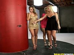 Having an erect young cock stick through the glory hole leaves these three hot blondes no other choice, but to wrap their lips and pussies around it.
