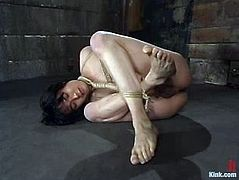 Sexy brunette girl ties Asian guy up. He lies on the floor in a very strange pose but he can't do anything about it.