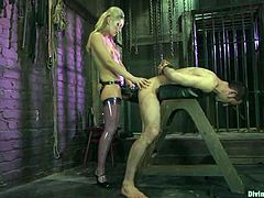 Superb blonde mistress in latex bodysuit ties the guy up. Then she also tortures his dick with bondage devices. After that she also drills his ass with a strap-on.