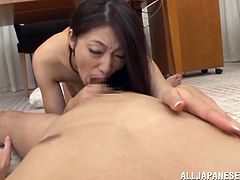 Adorable Japanese MILF kisses with a guy and then strips her negligee off. After that she sucks the guy off and fingers herself lying on the floor.