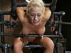 Lovely blonde girl with bog boob gets bounded with the help of a bondage device. Later on her master fixes claws to her nipples.