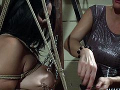 Pretty curvy black haired slave girl stands on dirty ground all naked with her arms and tits bounded. Voracious redhead mistress twists her nipples and attaches clamps to her tits.