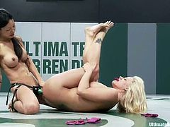 Two horny girls in bikini wrestle in a ring. White chick loses to Asian one. So, Holly sucks a strap-on and then gets toyed right in a ring.