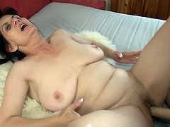 Plump black haired granny lies on her back stroking her huge tits while petite blondie puts on big strapon and starts fucking that time worn cunt missionary style.
