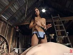 This dude gets tied up in some wooden barn by nasty brunette mistress. She tortures his dick and drills the ass with a strap-on.