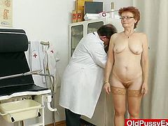This mature woman wearing glasses, and nothing else, is on the exam table with her legs spread wide and feet up in stirrups