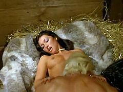 Dark haired hussy with beautiful face moans with pleasure while horny cowboy passionately fucks her soaking quim missionary style at the barnyard. Watch her cumming!