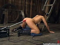 Hot brunette girl undresses in a wooden barn and toys herself with a vibrator. After that she gets her ass toyed deep and hard by the fucking machine.