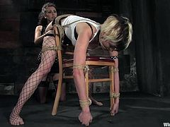 The girl with the crazy blond hair is totally tied before getting spanked, toyed and strapon fucked.
