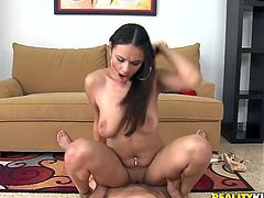 Get a boner watching this long haired brunette, with natural bazookas wearing shorts, while she gets drilled hard over a yellow couch!