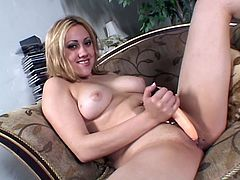 Blonde chick with big boobs lies on a sofa and toys her shaved pussy with two dildos of different size.