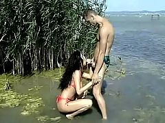 Naughty brunette girl sucks a dick and gets her juicy boobs licked outdoors. Later on this slut gets fucked in her pussy and ass right in the lake.