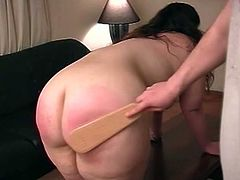 This BBW's pants and lace panties are pulled down, she is bent over a table, and her ass is spanked with a wooden paddle.