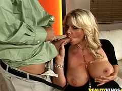 Big breasted blonde MILF sucks a cock and fondles her nipples at the same time. Then she get s fucked hard and deep from behind.