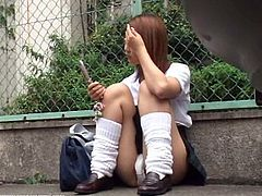 This Japanese girl sits on a sidewalk and sends text messages. Her crotch can be seen clearly. She has white panties on and her pussy lips are totally hairless.
