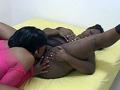 Both busty and dressed in fishnet body stockings, these ebony babes have fun licking each other's pussy.