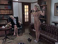 Dia Zerva and Maitresse Madeline are having BDSM fun indoors. The dominatrix puts her slave into irons and attaches nipple clamps to her tits.