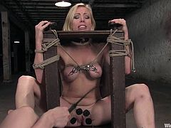 Different devices are used in this bondage session for the submissive girl who will end up fucked by her dominant's strapon dildo.