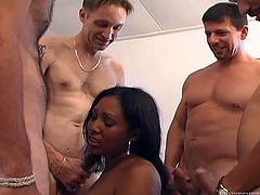 Salacious black chick is trying hard to satisfy a few dudes. She sucks and licks their pricks ardently and gets jizz on her lips and neck.