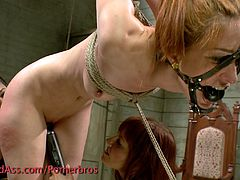Watch a sexy redhead temptress belle as she gets suspended by two horny mistresses. Watch them dildoing and licking her pussy into kingdom come.