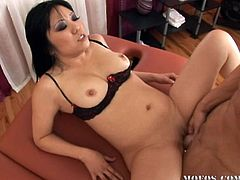Lustful Asian girl in red gown and black lingerie gives a massage. Then she sucks big dick and gets fucked hard in her shaved pussy.