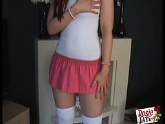 Rosie Jay is a British teen with red hair. She is wearing a cute little outfit, which she only partially takes off. She reveals her big boobies one by one.
