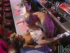 Blonde chick with nice ass and juicy tits eats in a diner. She talks to a chef and then has sex with him. He licks Serenity's pussy and then fucks her on a table. He also feeds the girl with his high caloric yogurt.