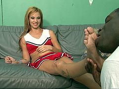 Charming blonde girl Sindy Rose wearing a cheerleader dress is getting naughty with some hairy black dude. She makes him eat her shaved pussy and then pokes her nice toes into the guy's mouth.