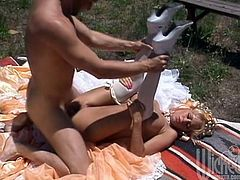 Slutty blonde Jenna Jameson wearing white stockings is having fun with some dude outdoors. She sucks and rubs the dude's prick and then lets him eat her pussy and fuck it doggy style.