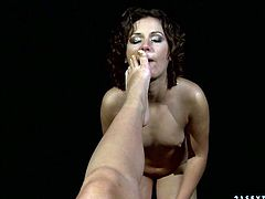 Curly brunette hooker with small tits poses in front of her mistress. She also shows cameltoe. Then, tough dominatrix orders sub girl to lick her toes.