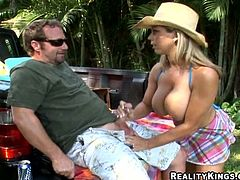 Amber Lynn shows off her huge boobs and gives a handjob. After that she gets fucked in a pickup truck. Amber gets titty fucked as well.