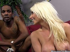 Stunning blonde girl with an engaging smile and juicy boobs poses for the camera with a Black guy. She has sperm on her face because this video was made right after sex.