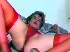 Horny woman in red lingerie and stockings fondles her pussy in a bedroom. Then she takes a silver dildo and starts to drill her wet vagina.